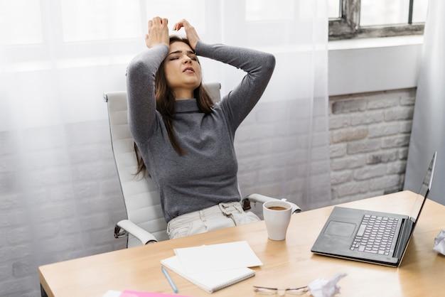 Geschäftsfrau, die frustriert schaut, während sie von zu hause aus arbeitet
