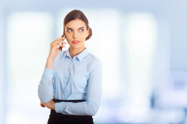 Geschäftsfrau, die gegen das bürofenster spricht am handy steht