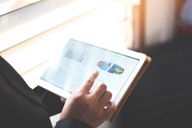 Geschäftsfrau, die geschäftsberichttablette unter verwendung des tablet-computer-geldes analysierend diagramme überprüfend arbeitet
