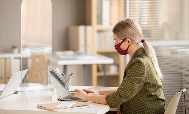 Geschäftsfrau, die gesichtsmaske im büro trägt