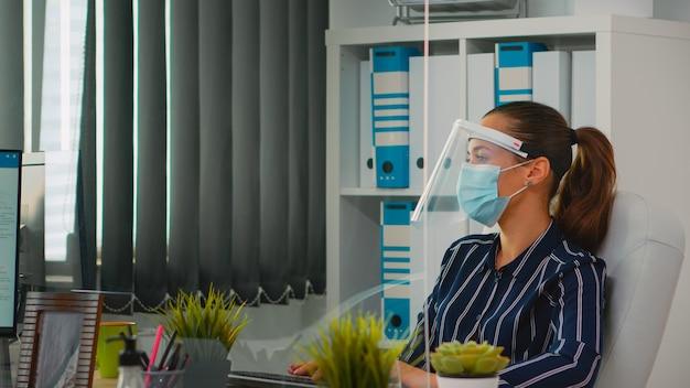 Geschäftsfrau, die gesichtsschutz zur vorbeugung gegen das tippen von coronavirus auf dem computer trägt, der in einem neuen normalen büro arbeitet. freiberufler, der in einem finanzunternehmen arbeitet und die soziale distanz während covid-19 respektiert