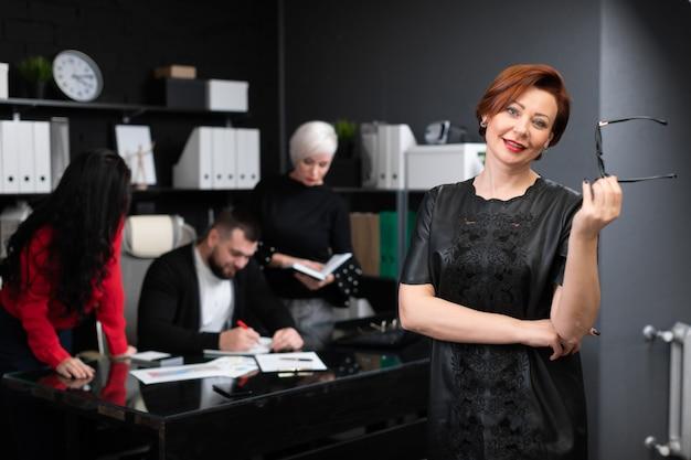 Geschäftsfrau, die gläser auf t-shirt von den büroangestellten besprechen projekt hält