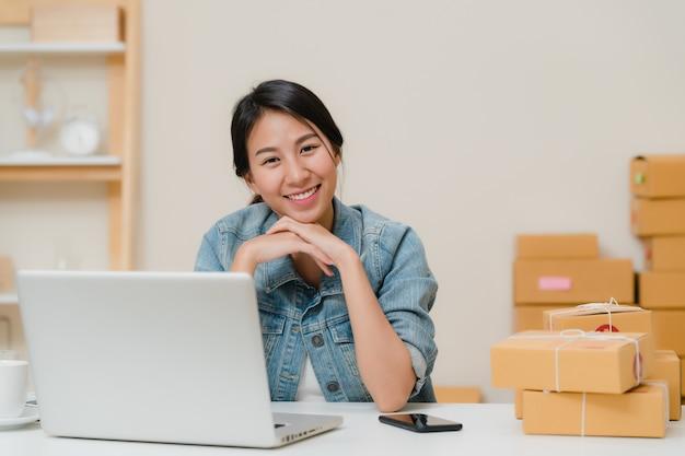 Geschäftsfrau, die glücklich lächelt und zur kamera beim in ihrem büro zu hause arbeiten schaut.