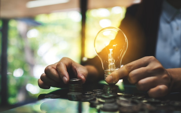 Geschäftsfrau, die glühbirne hält, während münzen auf tisch für energie- und geldkonzept stapeln