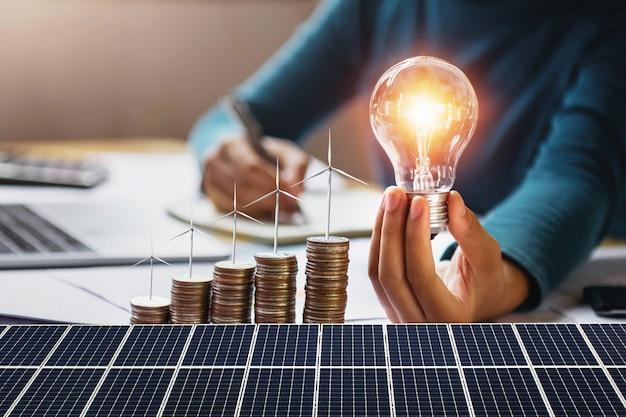 Geschäftsfrau, die glühlampe mit turbine auf münzen und sonnenkollektor hält. konzept energieeinsparung und finanzbuchhaltung