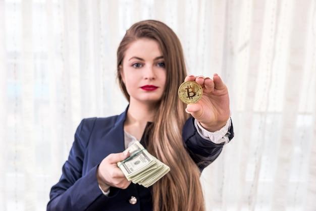 Geschäftsfrau, die goldenes bitcoin und dollarbündel zeigt