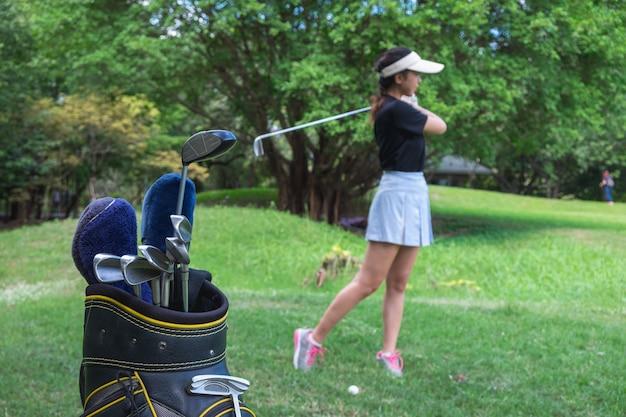 Geschäftsfrau, die golf auf der grünen wiese spielt