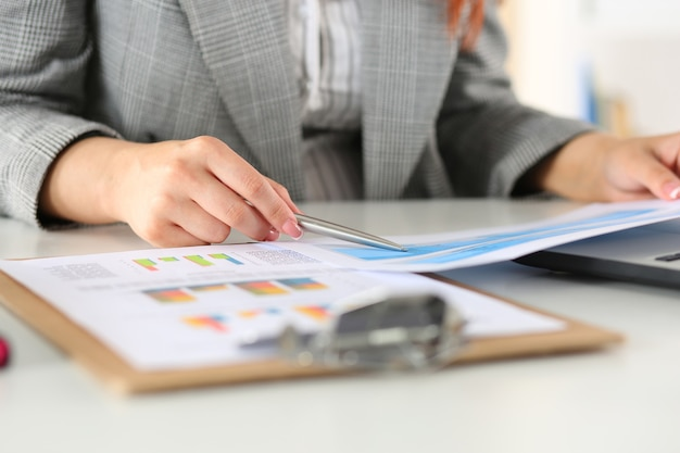 Geschäftsfrau, die grafiken betrachtet. manager oder auditor lesen berichte. konzept für finanzplanung, geschäftsanalyse und projektmanagement.
