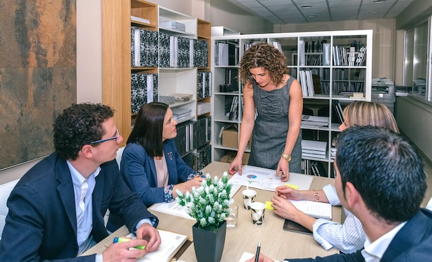 Geschäftsfrau, die grafiken in einem geschäftstreffen zur teamarbeit sucht, die am tisch in der firmenzentrale sitzt