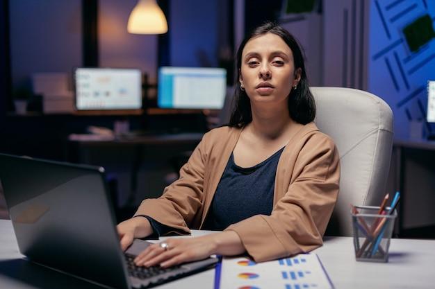 Geschäftsfrau, die hände auf der laptoptastatur hält, die kamera betrachtet. intelligente frau, die im laufe der späten nachtstunden an ihrem arbeitsplatz sitzt und ihren job macht.