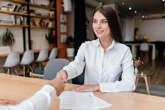 Geschäftsfrau, die hände auf einem abkommen rüttelt, nachdem vertrag unterzeichnet worden ist