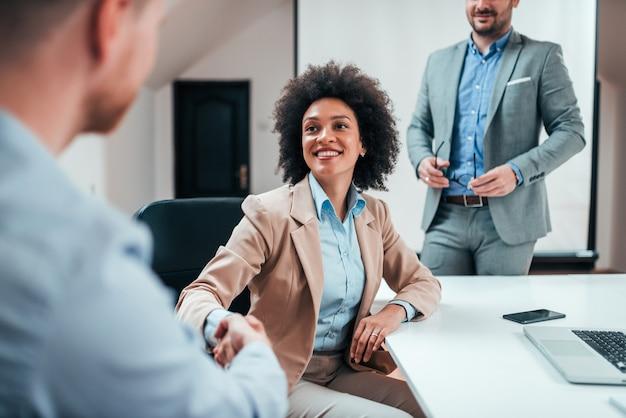 Geschäftsfrau, die hände mit anderem angestellten auf einer unternehmenssitzung rüttelt.