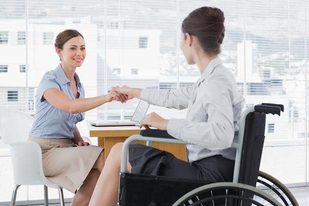 Geschäftsfrau, die hände mit behindertem kollegen rüttelt
