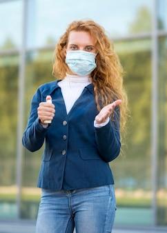 Geschäftsfrau, die händedesinfektionsmittel verwendet und medizinische maske trägt
