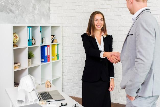 Geschäftsfrau, die hand mit einem mann rüttelt