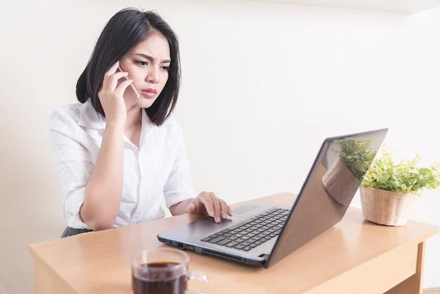 Geschäftsfrau, die handy bei der anwendung des computerlaptops am schreibtisch im büro verwendet.