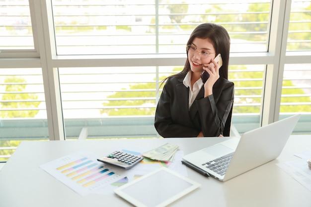 Geschäftsfrau, die handy und computer beim arbeiten an firmenzusammenfassungsbericht mit diagramm verwendet