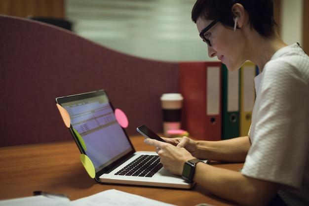 Geschäftsfrau, die handy während der arbeit am laptop verwendet