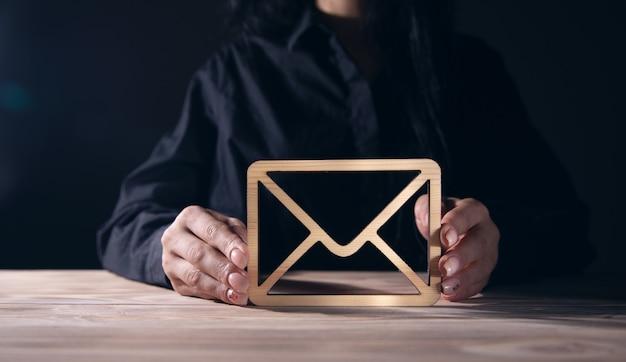 Geschäftsfrau, die hölzernes umschlagbriefzeichen hält