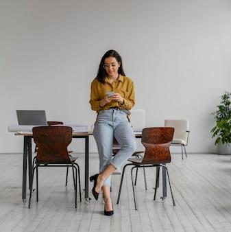 Geschäftsfrau, die ihr telefon bei der arbeit überprüft