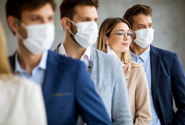 Geschäftsfrau, die ihre schützende gesichtsmaske abnimmt und die kamera mit ihren teammitgliedern betrachtet, die in der linie am büro stehen