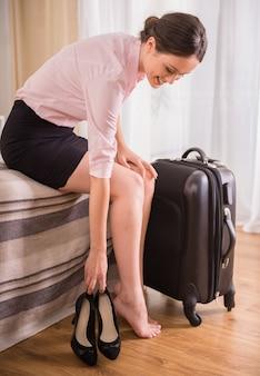 Geschäftsfrau, die ihre schuhe beim sitzen auf bett niederlegt.