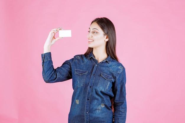 Geschäftsfrau, die ihre visitenkarte hält und betrachtet