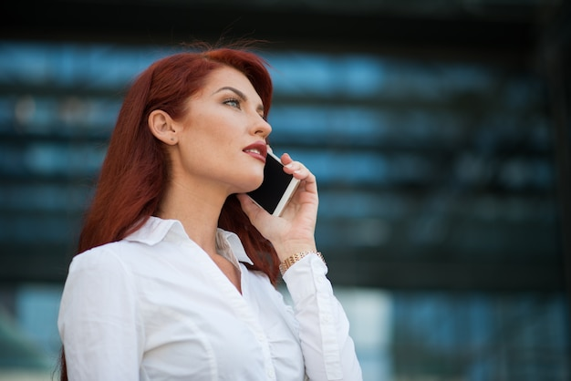 Geschäftsfrau, die ihren handy vor ihrem büro verwendet