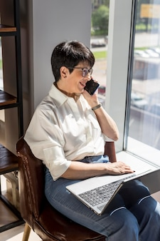 Geschäftsfrau, die ihren laptop hält und am telefon spricht