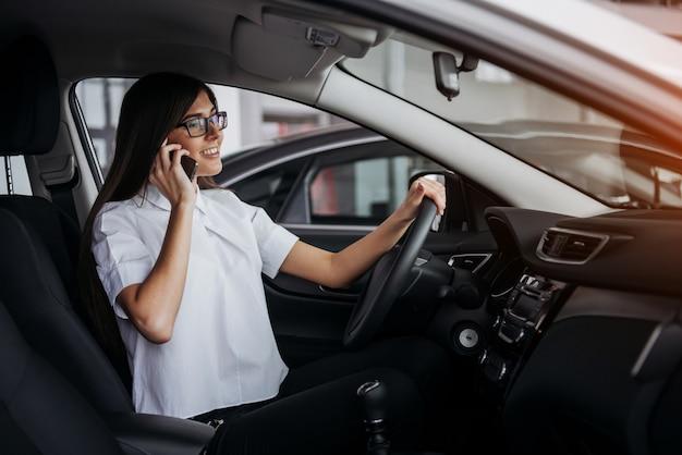 Geschäftsfrau, die im auto am telefon spricht.