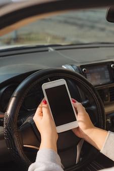 Geschäftsfrau, die im auto sitzt und ihr smartphone benutzt. modellbild mit fahrerin und telefonbildschirm
