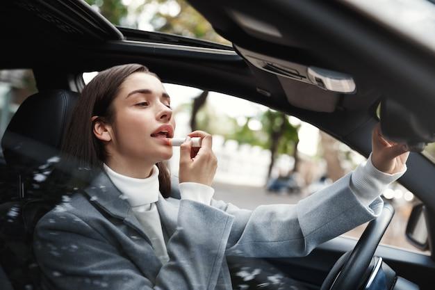 Geschäftsfrau, die im auto sitzt und lippenstift benutzt, sich im rückspiegel betrachtend, um make-up zu überprüfen