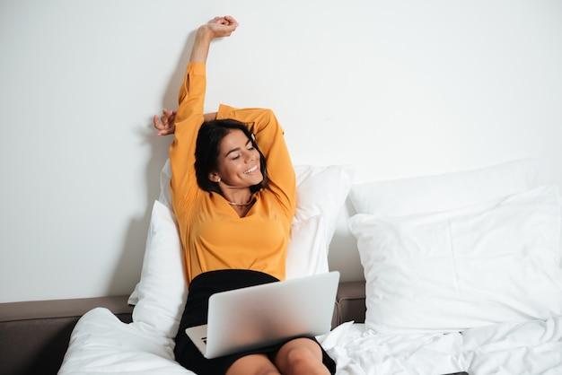 Geschäftsfrau, die im bett mit laptop liegt und hände streckt