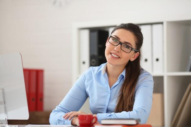 Geschäftsfrau, die im büro am tisch sitzt