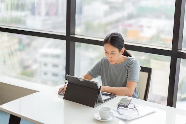 Geschäftsfrau, die im büro an ihrem tablet arbeitet