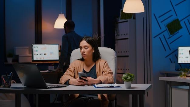 Geschäftsfrau, die im büro eines startup-unternehmens arbeitet, das am schreibtisch sitzt