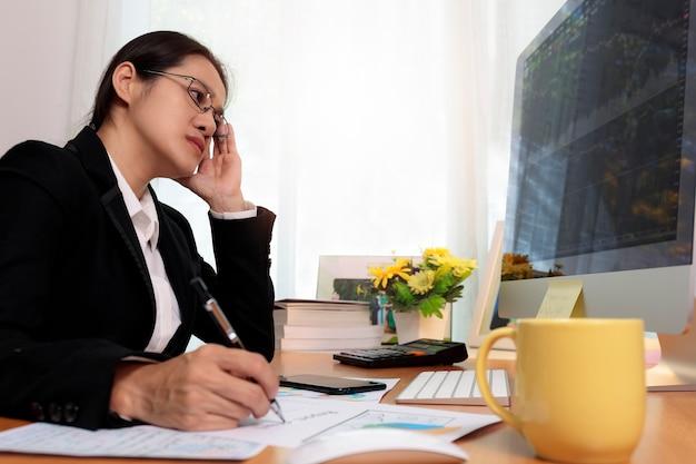 Geschäftsfrau, die im büro mit computer thinking analysis stock chart arbeitet. geschäftsleute, die zu hause mit pc-bildschirm arbeiten. business und finanzen, work-at-home-konzept