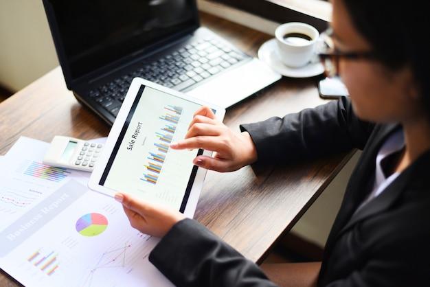 Geschäftsfrau, die im büro mit der prüfung des geschäftsberichts unter verwendung des tablet-computer-technologielaptops mit taschenrechner arbeitet.