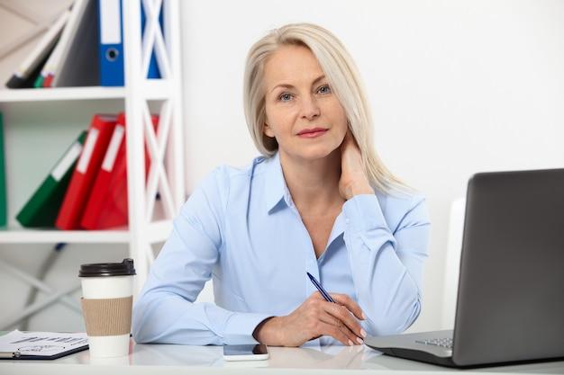 Geschäftsfrau, die im büro mit dokumenten und laptop arbeitet.