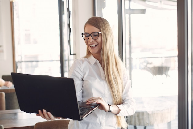 Geschäftsfrau, die im büro mit einem laptop steht
