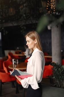 Geschäftsfrau, die im büro mit einem notizbuch steht