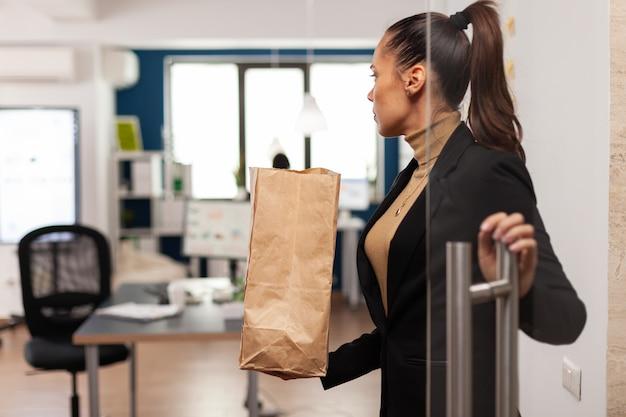 Geschäftsfrau, die im büro mit essen zum mitnehmen ankommt
