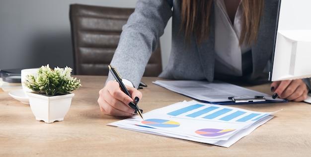 Geschäftsfrau, die im büro mit grafiken und diagrammen arbeitet.