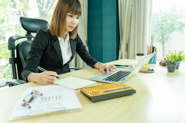 Geschäftsfrau, die im büro mit laptop- und papierdokumenten auf schreibtisch arbeitet