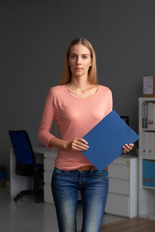 Geschäftsfrau, die im büro mit papierordner steht