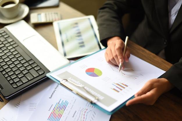 Geschäftsfrau, die im büro mit schreibtisch des geschäftsberichts mit laptoptablette und kaffeetasse auf dem tisch überprüfen / berichtsgeld vorbereiten, das diagramme analysiert