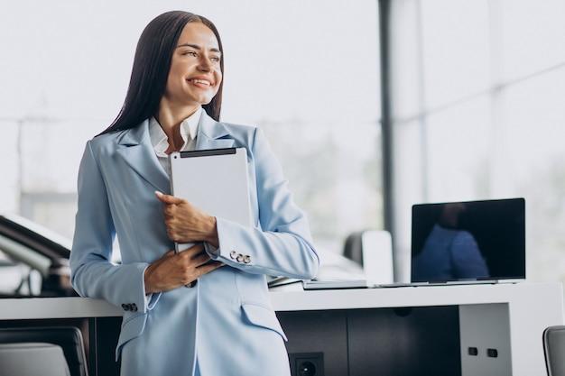 Geschäftsfrau, die im büro mit tablette in den händen steht