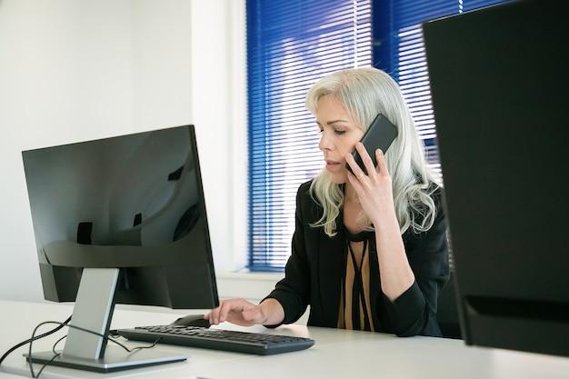 Geschäftsfrau, die im büro sitzt und am telefon spricht. grauhaariger, selbstbewusster mitarbeiter, der auf der computertastatur tippt und die arbeit mit dem kunden über das smartphone bespricht. geschäfts- und kommunikationskonzept