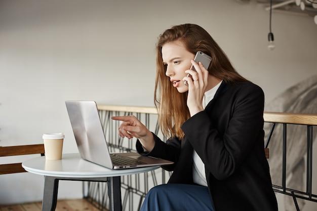 Geschäftsfrau, die im café arbeitet, am telefon spricht und laptop betrachtet
