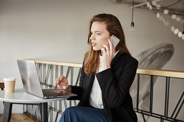 Geschäftsfrau, die im café arbeitet, anrufe entgegennimmt und laptop betrachtet